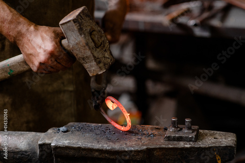 Foto Blacksmith is processing a hot metal object of a spiral shape at anvil in a workshop