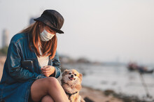 Woman Wearing Surgical Mask For Prevent Coronavirus Outbreak Travel On The Beach At Sunset Time In Thailand.