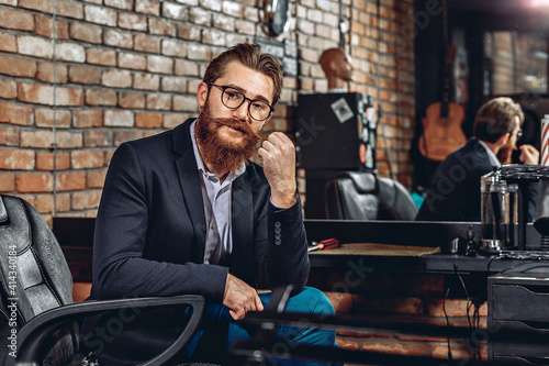 Papel de parede Portrait of a stylish attractive man in a jacket, glasses, with a mustache and a beard sitting on a leather armchair and looking at the camera in a barber shop