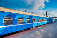 Line Of Standard Blue Railway Carriages At Station Platform At Daytime.