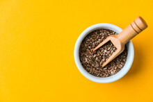 Wooden Spoon With Flax Seeds Lies In A White Mortar On A Yellow Background. Healthy Eating. Keto Diet.