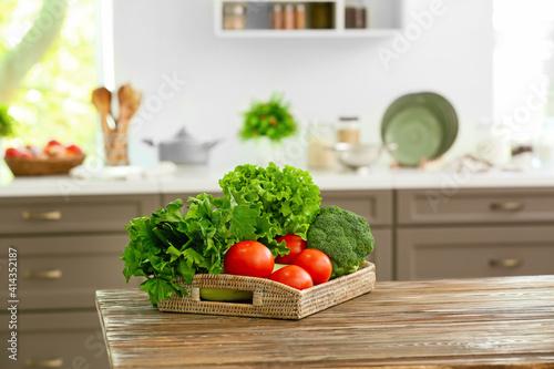 Fototapeta Tray with vegetables on table in modern kitchen obraz