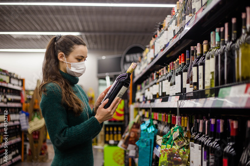 Young woman wearing medical mask is choosing wine in the supermarket. © glebcallfives