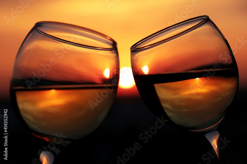 Silhouettes of two glasses with white wine on sunset background, selective focus. Couple clink glasses, concept of celebration, romantic evening, love date © Oleg