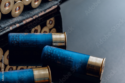 Fotografiet Rifle bullets or cartridges on black shiny background