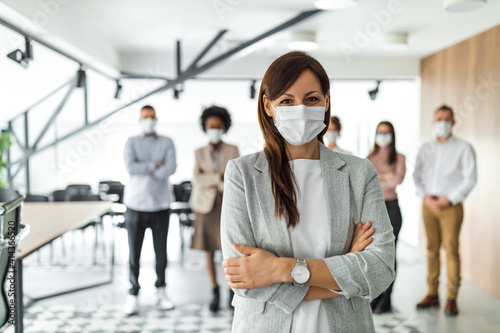 Obraz Business group of people, standing behind female boss. - fototapety do salonu