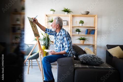 Foto Smiling mature man painting on canvas at home
