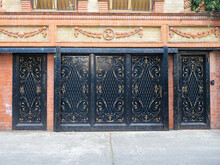 Black Iron Garage Gates And Doors With An Elaborate Gilded Pattern Of Monograms And Bars In A Brick House With Ornamental Masonry