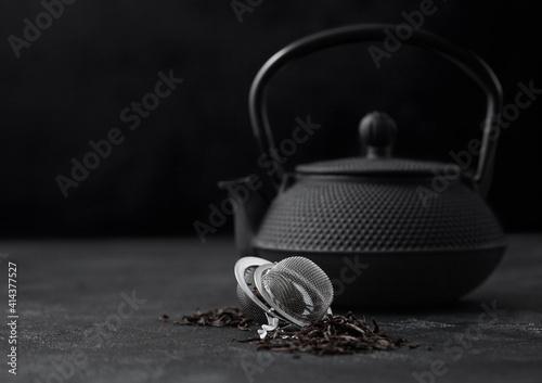 Iron japanese teapot with black loose tea with strainer infuser on dark. © DenisMArt