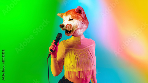 Celebrity. Talented dog, professional musician performing on multicoloted background in neon light. Concept of music, hobby, festival, contemporary art collage. Modern design. Copyspace. © master1305