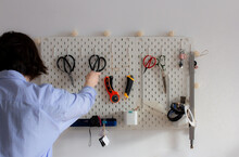 Woman Craftsman In Sewing Workshop And Wall Of Tools With Scissors, Knives, Tapes, Ruler, Designer Working In Atelier