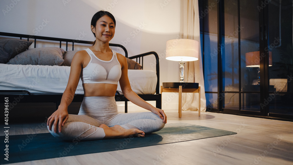 Fototapeta Young Asia lady in sportswear doing yoga exercise working out in living room at home at night. Sport and recreation activity, social distancing, quarantine for corona virus prevention concept.