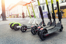 Many Modern Electric Kick Scooters Sharing Parked On City Street. Self-service Stree Transport Rental Service. Rent Urban Mobility Vehicle With Smartphone Application. Zero Emission Green Eco Energy.