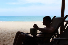 A Man Sits On The Beach With A Coconut In His Hands Against The Background Of The Sea
