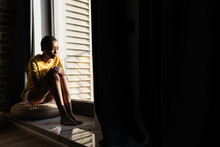 Attractive Young African Woman Sitting On A Windowsill