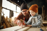 Little boy with father creating woodwork in workshop