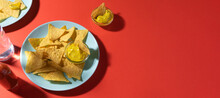 Nachos Chips With Cheese Sauce On Blue Plate On Red Background With Copy Space. Food Photo Banner Format. Concept Roadside Cafe Or Truck Stop Fast Food