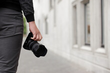 Modern Dslr Camera In Male Hands, Copy Space Over Concrete Building Background