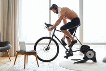Athletic Young Man Listening To Music And Riding Stationery Bike