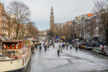 People Ice Scating On Frozen Canal In City Center Of Amsterdam