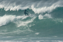 Surfer Carving And Performing Tricks On Huge Blue Waves In Newquay, Cornwall - Southwest England