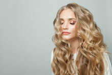 Attractive Woman With Long Blonde Healthy Curly Hair On White Background