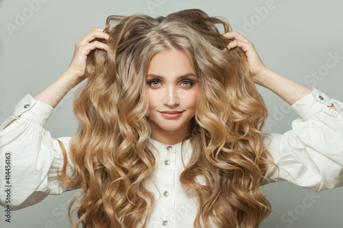 Tela Beautiful smiling woman touching her long blonde healthy curly hair on white bac