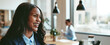 Laughing young African American businesswoman walking through an office