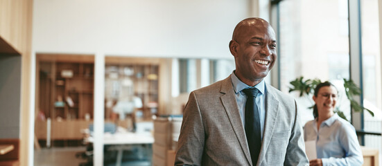 African American businessman laughing while walking through a modern office