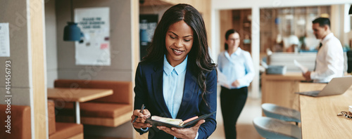 Cuadros en Lienzo Smiling African American businesswoman walking through an office writing notes