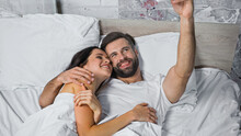 Cheerful Man Sticking Out Tongue While Lying With Smiling Woman In Bed
