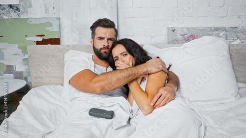 Fototapeta worried couple hugging while watching movie in bed obraz na płótnie