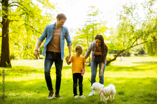 Obraz na plátně Happy family with cute bichon dog in the park