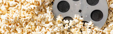 Top View Of Film Bobbin On Airy Delicious Popcorn, Banner, Cinema Concept