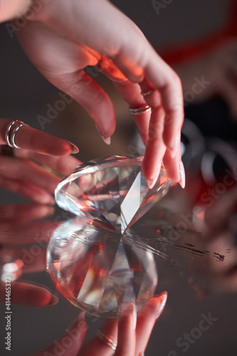 Beauty Woman holds big diamond in hand while lying on table. Beautiful hands, professional manicure, large brilliant © angel_nt