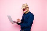 Euphoric man with dinosaur head using laptop