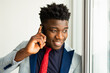 handsome young african man in suit with mobile phone