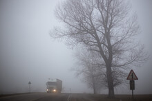 The Truck Is Driving On A Foggy Road With Bare Trees, Dangerous Weather Conditions. Driving In Poor Visibility