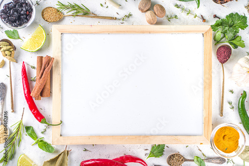 Fresh herbs, dried colorful spices. Cooking background flatlay with variety spices, herbs pepper, vanilla bean, cinnamon, basil, rosemary, chilli red green peppers, mint, parsley White table top view