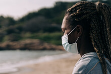 African Woman Doing Yoga And Meditating Outdoors At The Beach During Coronavirus Outbreak - Focus On Face