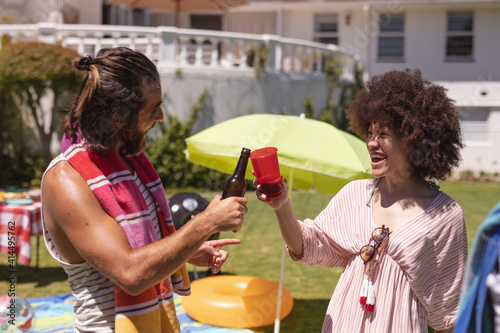 Two diverse male and female friends drinking and making a toast at a pool party