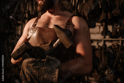 Tableau sur Toile Blacksmith in a leather apron in a forge holding two crossed hammers close up
