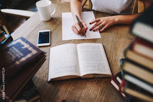 Obraz Woman writing notes on sheet of paper - fototapety do salonu