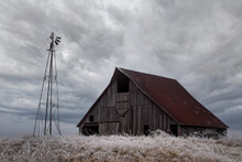 An Old Barn Next To A Broken Windmill On A Stormy, Icey, Dramatic Day