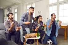 Cheering, Shouting Young Men Watching Exciting Sports Game. Group Of Friends Enjoying World Cup On TV At Home, Eating Pizza And Chips, Drinking Beer And Celebrating Favorite Soccer Team Scoring A Goal