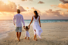 A Happy Family Holding Hands On Vacation Walks Down A Beach During Sunset Time