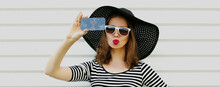 Portrait Of Beautiful Woman Taking Selfie Picture By Smartphone Wearing A Black Round Summer Hat On A White Background