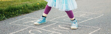 Closeup Of Child Girl Playing Jumping Hopscotch Outdoors. Funny Activity Game For Kids On Playground. Summer Backyard Street Sport For Children. Happy Childhood Lifestyle. Web Banner Header.