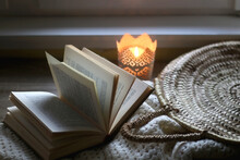 Open Book, Woven Basket, Crochet Blanket And Lit Candle. Cozy Details At Home. Selective Focus.
