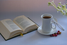 Morning Still Life: An Unusual-shaped White Cup With Coffee, A Small White Ceramic Spoon, Multicolored Sea Stones Candy, A Miniature Volume Of Poetry, A Branch Of Ornithogalum Balansae.